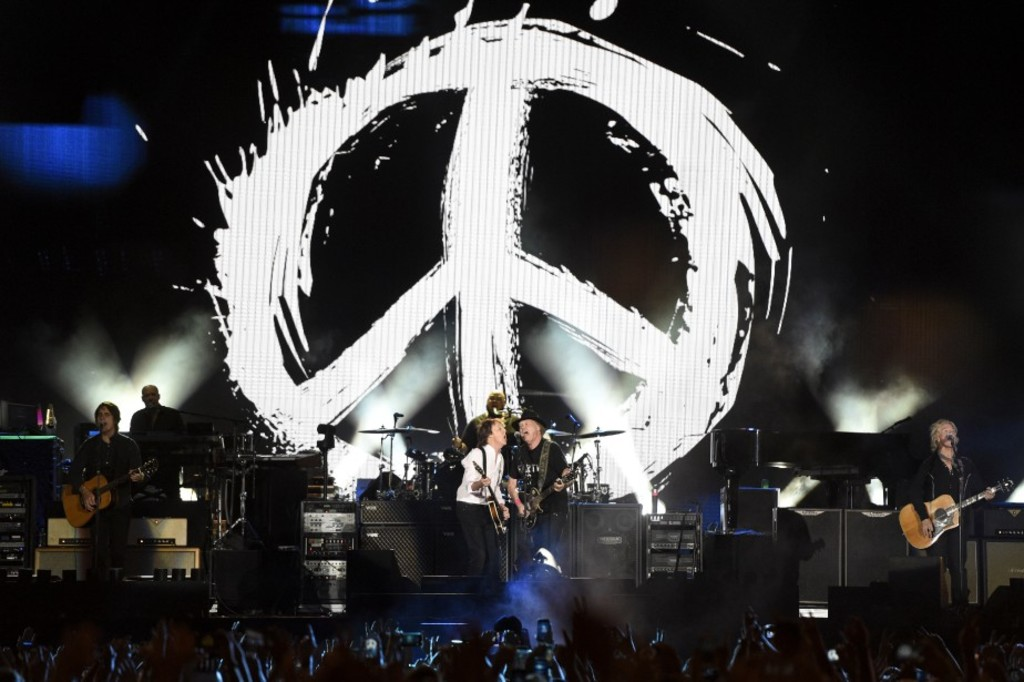 Paul McCartney, center left, is joined at the microphone by Neil Young during McCartney's performance on day 2 of the 2016 Desert Trip music festival at Empire Polo Field on Saturday, Oct. 8, 2016, in Indio, Calif. (Photo by Chris Pizzello/Invision/AP)