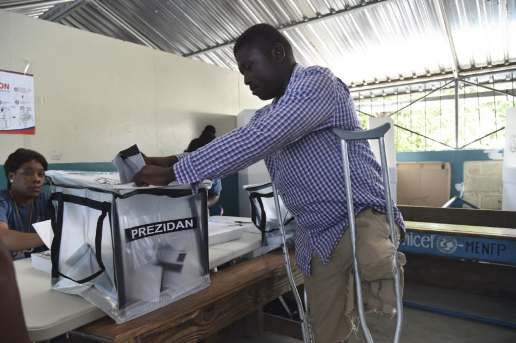 A voter casts his ballot at a polling station at the Lycee National of Petion Ville in the Haitian capital Port-au-Prince, on November 20, 2016 during the presidential and legislative elections.Haitians go to the polls Sunday to elect a president and lawmakers, in hopes of restoring the country to constitutional order after more than a year of political crisis. Nearly 6.2 million voters are eligible to cast their ballots to choose among a vast field of 27 presidential candidates. / AFP PHOTO / HECTOR RETAMAL