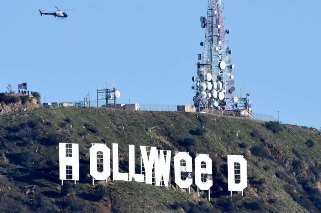 """The famous Hollywood sign reads """"Hollyweed"""" after it was vandalized, January 1, 2017.  Police said unidentified thrill-seekers had climbed up and arranged tarps over the two letter """"O's"""" to make them look like """"E's,"""" CBS affiliate KCAL reported. Each letter is 45 feet (13.7 meters) high, so the feat would have required not just bravado but considerable athleticism.  / AFP PHOTO / Gene Blevins"""
