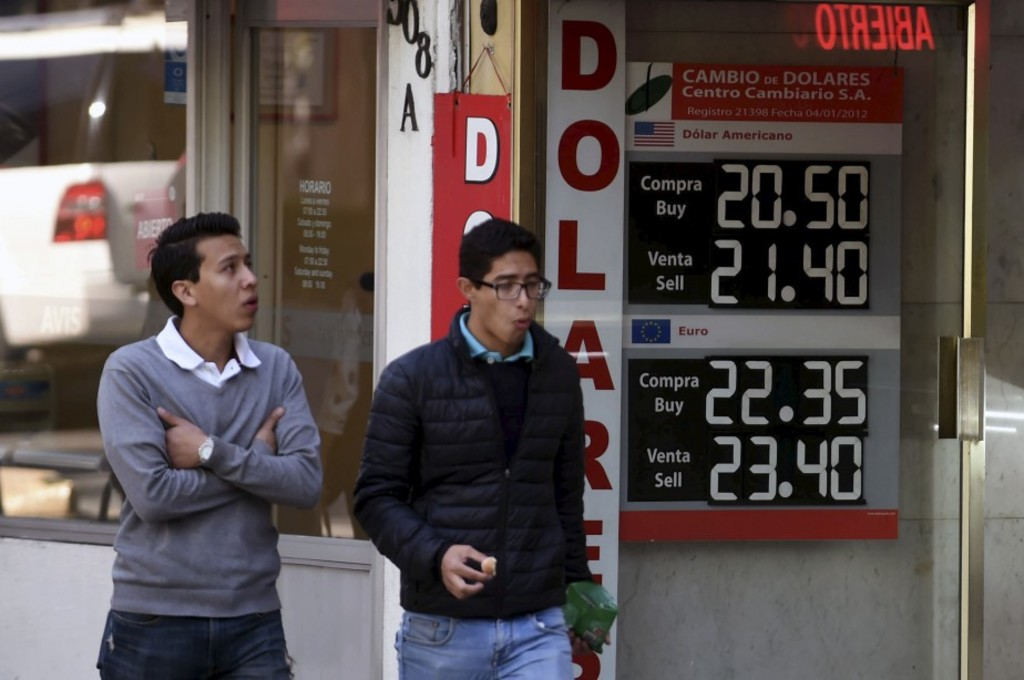 A currency board shows the US dollar exchange rate at a bureau de change in Mexico City on January 11, 2017.Mexico's peso hit a new low on Wednesday after US President-elect Donald Trump vowed to make the country pay for a huge border wall and to tax companies that ship jobs abroad. The Mexican currency shed 0.9 percent, trading at 22.20 pesos per dollar after hitting a historic low 22 pesos per greenback on Tuesday, according to private bank Citibanamex. / AFP PHOTO / Alfredo ESTRELLA