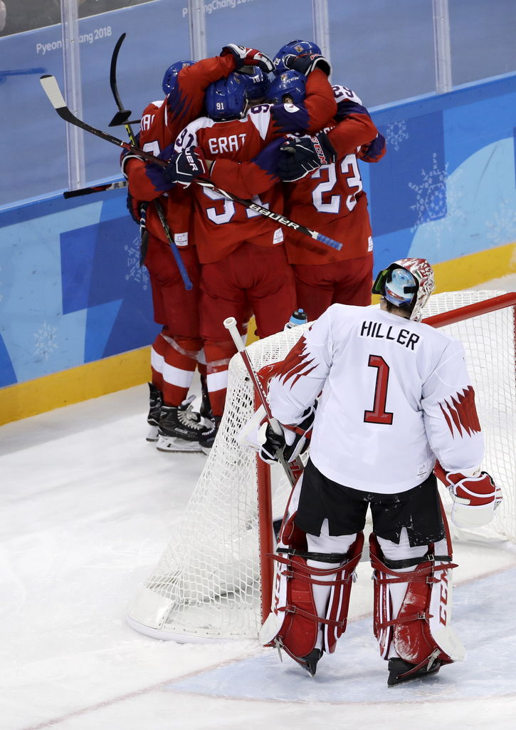 Players from the Czech Republic celebrate after Dominik Kubalik scores a goal as goalie Jonas Hiller (1), of Switzerland, looks on during the third period of the preliminary round of the men's hockey game at the 2018 Winter Olympics in Gangneung, South Korea, Sunday, Feb. 18, 2018.