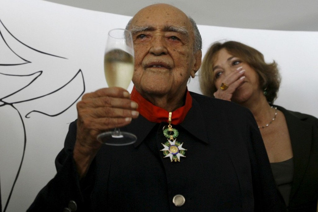 Brazil's architect Oscar Niemeyer holds a glass of champagne as his wife Vera reacts after he was honored by France's ambassador to Brazil Antoine Pouilliete, unseen, in commemoration of his 100th birthday in Rio de Janeiro, Wednesday, Dec. 12, 2007.  Niemeyer was born on Dec. 15, 1907. (AP Photo/Ricardo Moraes)