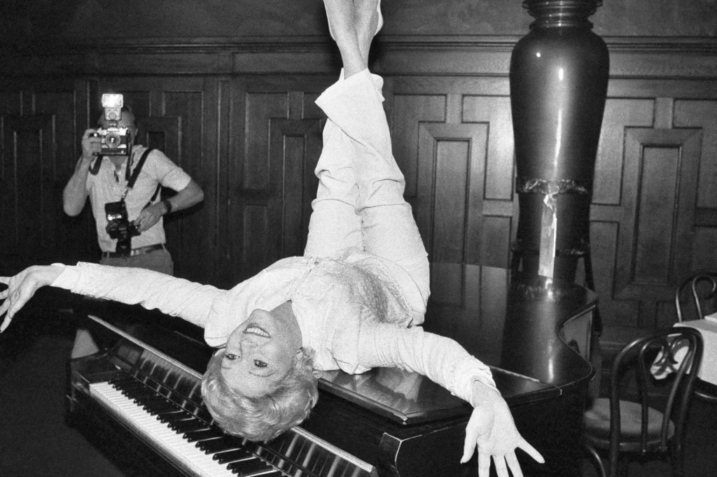 Debbie Reynolds pose sur un piano dans un restaurant de New York, en 1982.