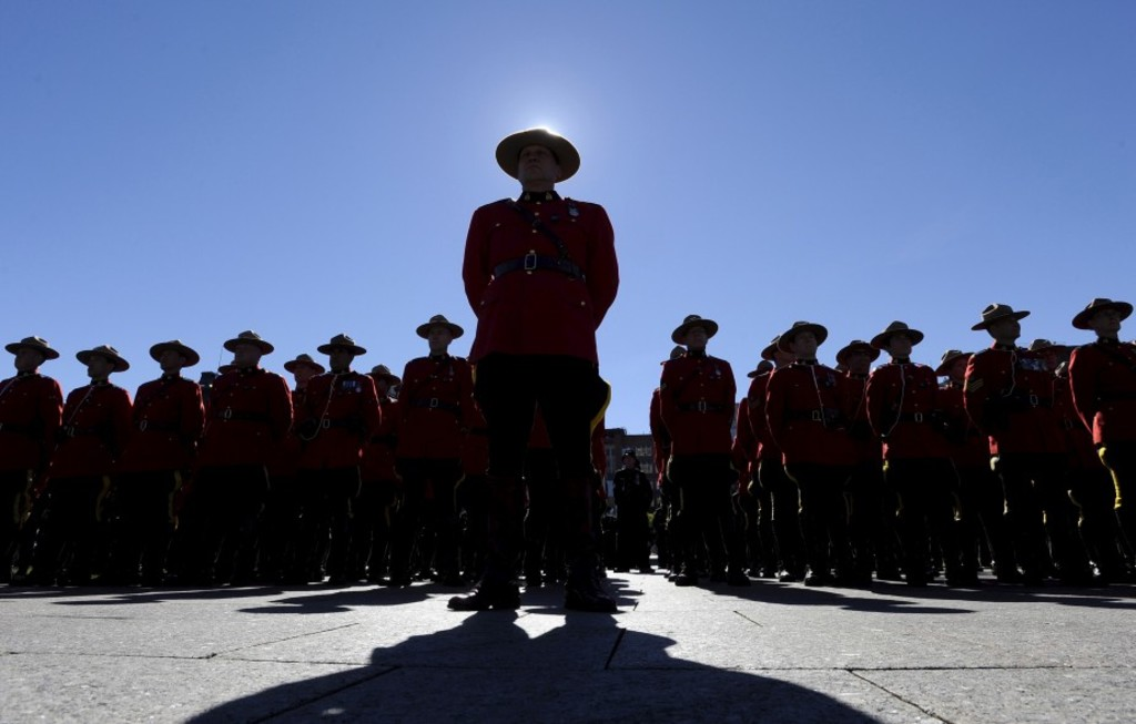 RCMP officers stand at attention at the Canadian Police and Peace Officers' Memorial Service on Parliament Hill in Ottawa on Sunday, Sept. 25, 2016. THE CANADIAN PRESS/Justin Tang