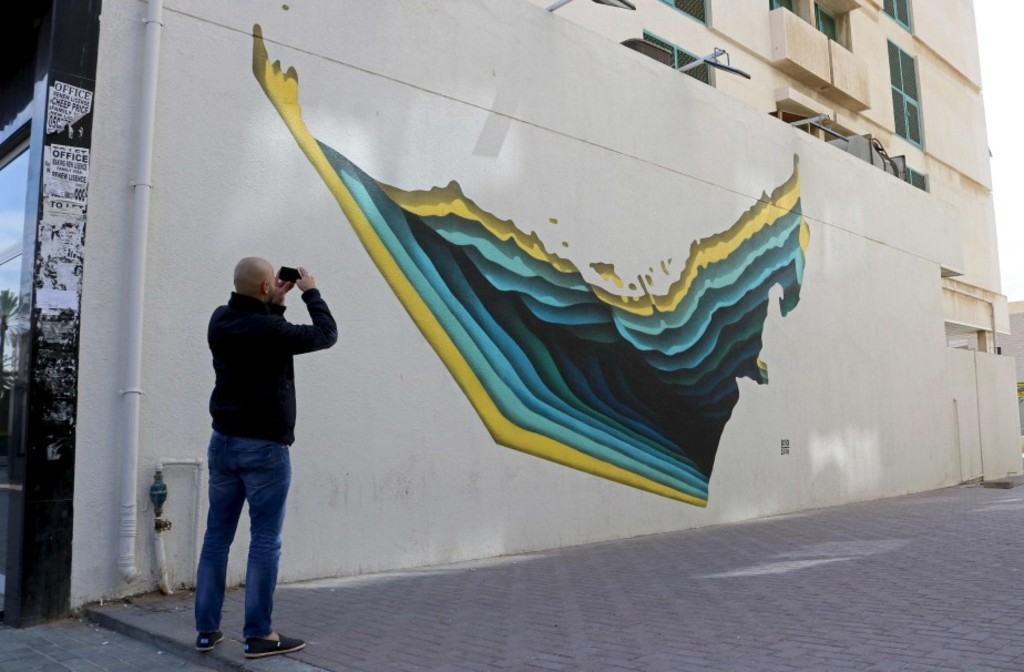 Un passant prend en photo un graffiti réalisé par l'artiste tunisien The Inkman.