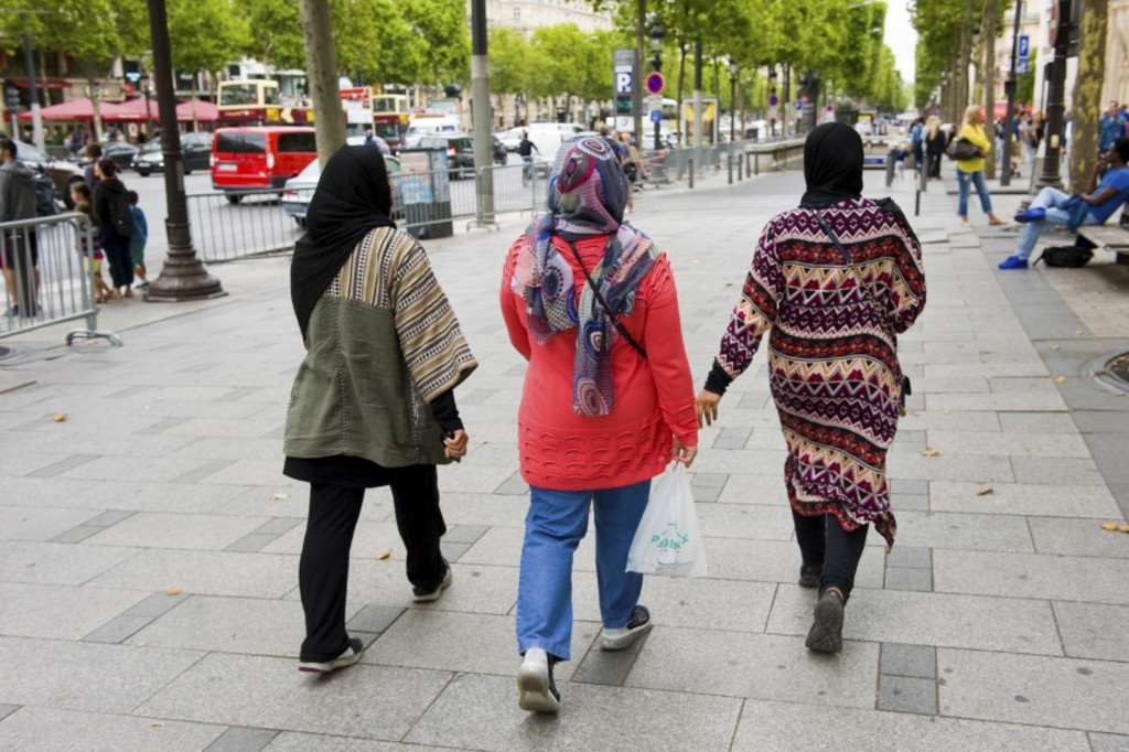 Photo: 123RF/ Robert Hoetink - PARIS, FRANCE - JULY 28, 2015: Three muslim woman with head scarf are walking on the Champs-Elysees in Paris in France
