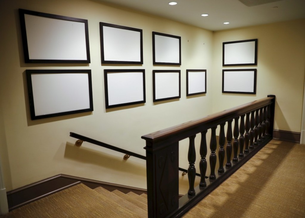 Photos of President Barack Obama and his family, that for years have lined the walls of corridors in the West Wing of the White House in Washington, are now blank and empty, Thursday, Jan. 19, 2017. Only a skeleton staff remained at the White House on Thursday, creating an eerily quiet feeling in the normally bustling West Wing. Many desks and offices were already empty, having been vacated by staffers who have departed over the past few weeks. Those staffers still left were packing up their desks, handing in their phones and saying teary farewells to their colleagues. (AP Photo/Pablo Martinez Monsivais)