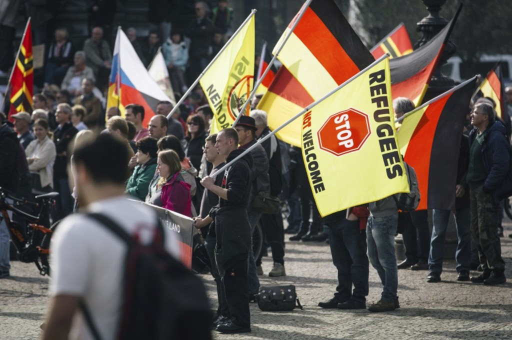Supporters of the anti-immigrant Pegida movement (Patriotic Europeans Against the Islamisation of the Occident) mark the second year of existence as they demonstrate in Dresden, eastern Germany, on October 2016, and Dresden, a Baroque city in Germany's ex-communist east, is the birthplace of the anti-immigration PEGIDA street movement. / AFP PHOTO / dpa / Oliver Killig / Germany OUT