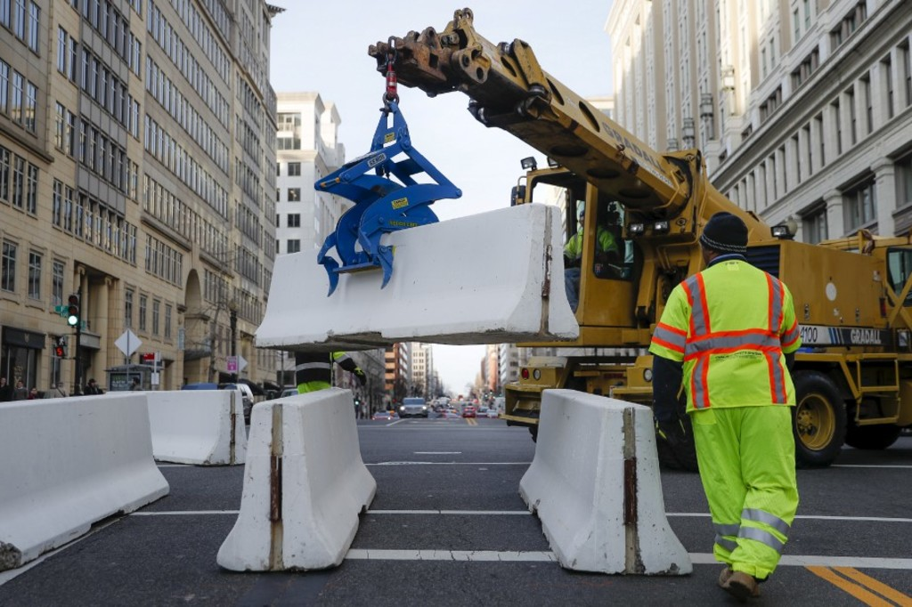 Workers place concrete barricades on a side street leading to Pennsylvania Avenue in Washington, Thursday, Jan. 19, 2017, as security tightens ahead of Friday's presidential inauguration. (AP Photo/John Minchillo)