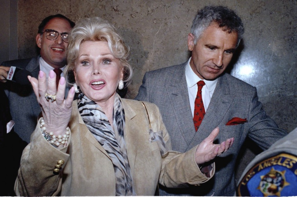 FILE - In a May 1, 1990 file photo, Zsa Zsa Gabor gestures as she while answering questions as she leaves the Beverly Hills courtroom where judge Charles Rubin ruled that she violated her probation. Gabor was ordered to complete her community service at a Venice homeless shelter, with an additional 60 hours. At right is her husband Frederick von Anhalt. Gabor died Sunday, Dec. 18, 2016, of a heart attack at her Bel-Air home, her husband, Prince Frederic von Anhalt, said. She was 99.(AP Photo/Kevork Djansezian, File)