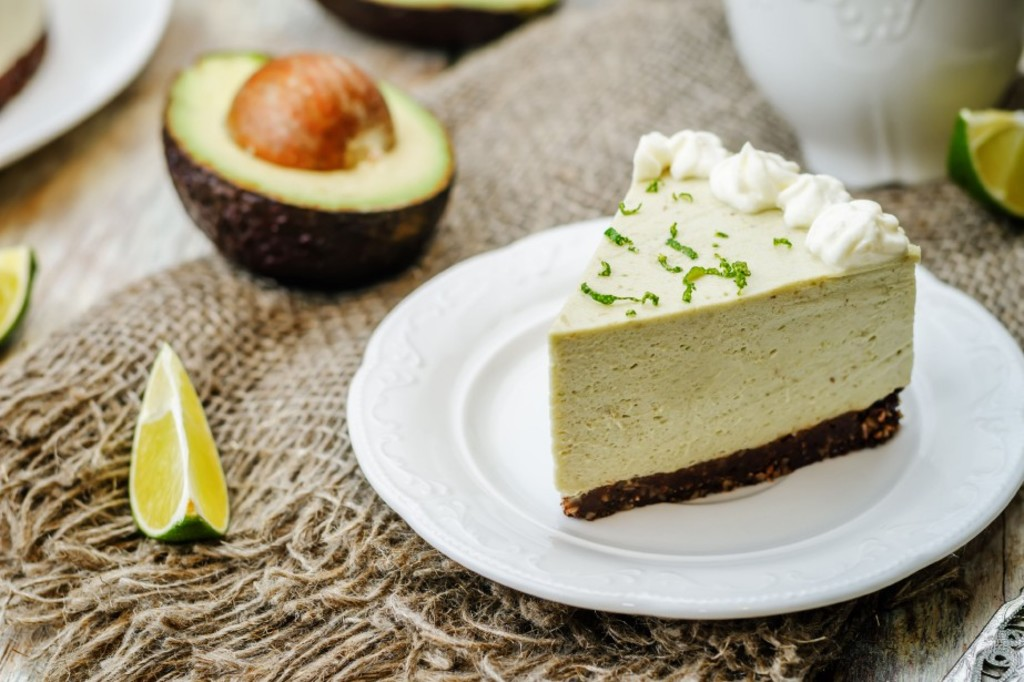 47945978 - avocado lime cheesecake on a white wood background.